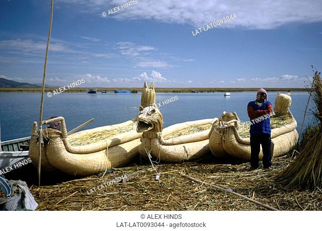 A man in a traditional knitted hat stands by three woven reed boats on a reed island inhabited by the Uros peoples at the water's edge. Lake