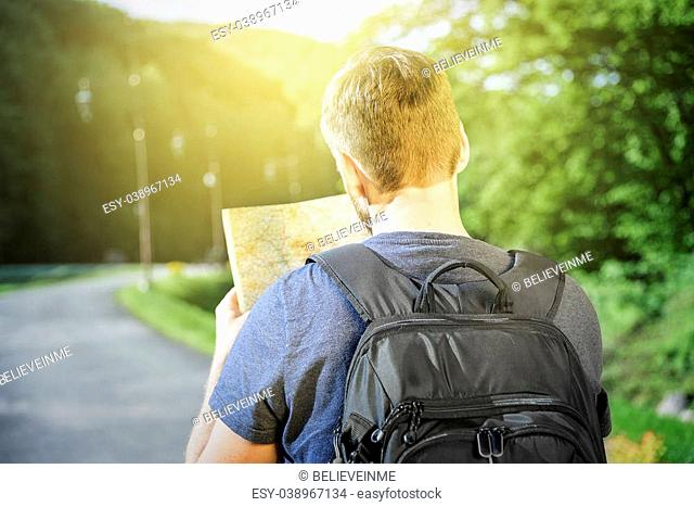 Traveler man searching right direction on map, freedom and active lifestyle concept