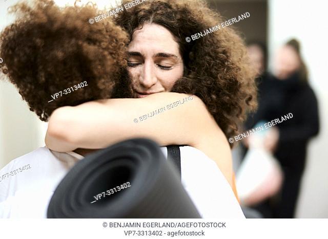 two women hugging in fitness studio