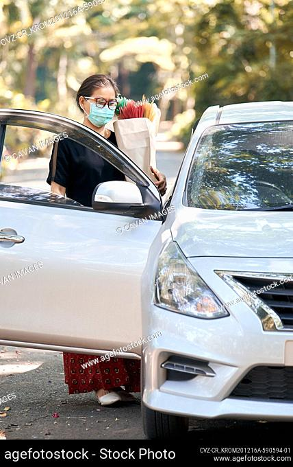 Woman hold a paper bag after shopping during COVID-19 pandemic