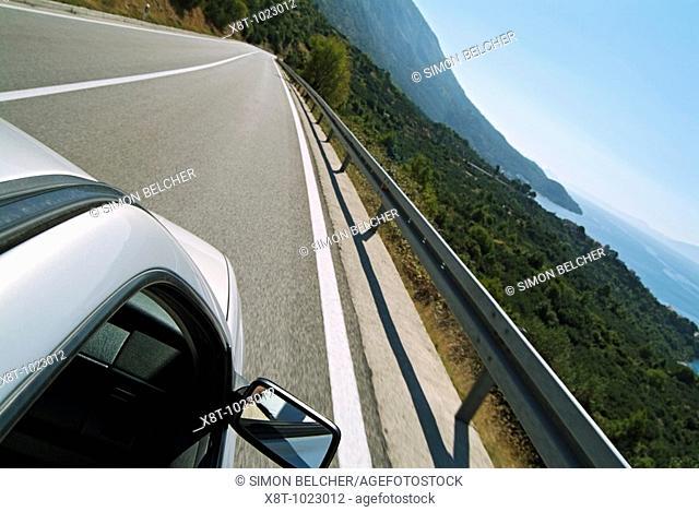 Croatia, Dalmation Coast, Car Driving on a Highway Overlooking the Adriatic Coastline