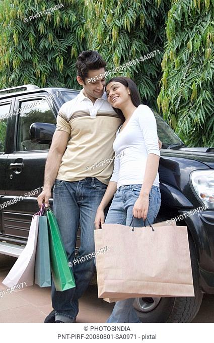 Couple carrying shopping bags and smiling
