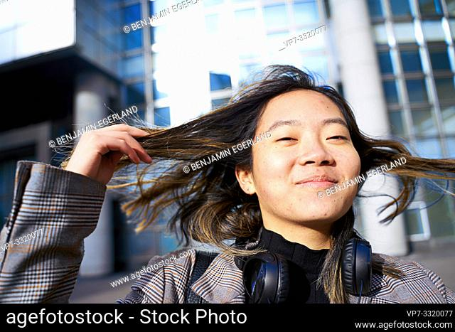 young sanguine Asian woman playing with hairs, in business district in Paris, France