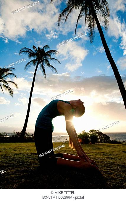 Woman practicing yoga in grassy field