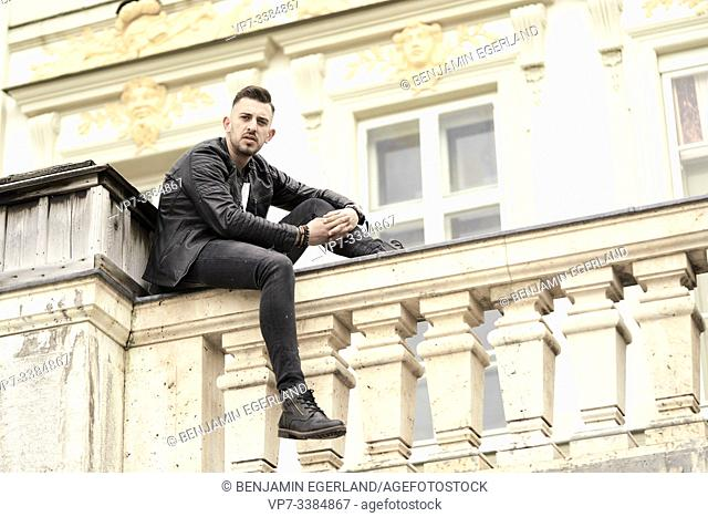 Man sitting on bannister, in Munich, Germany