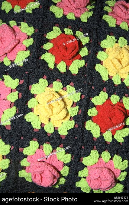 Crocheted flowers on cushion cover