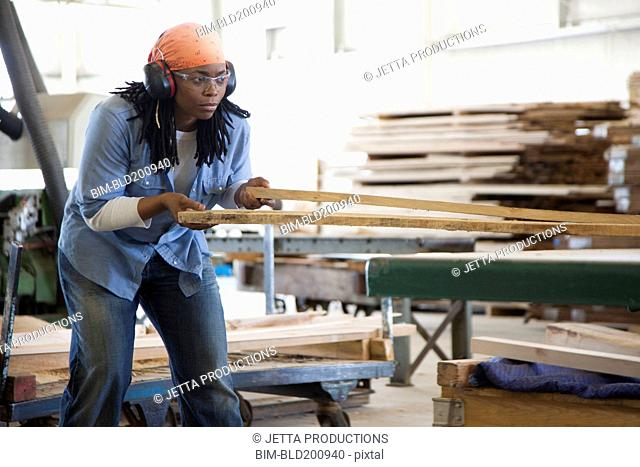 Black worker working with lumber in factory