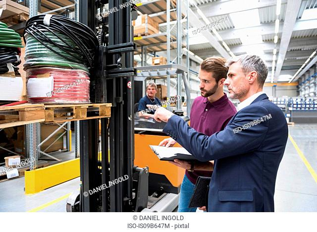 Manager pointing at forklift truck pallet in distribution warehouse