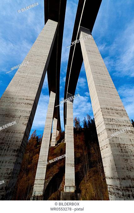 A high freeway bridge and concrete pillars seen from below