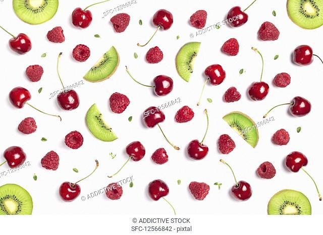 Cherry, raspberry and kiwi slices over white background