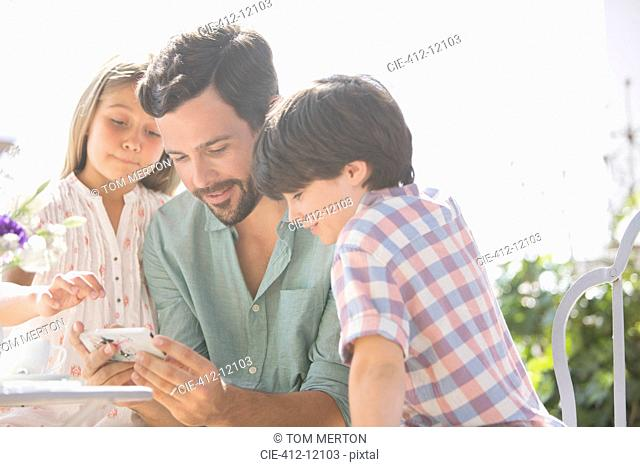 Father and children using cell phone outdoors