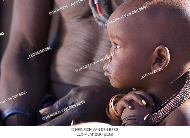 Profile view of a Himba child and torso of man, Van Zyl,Äôs Pass area, Kaokoland, Namibia