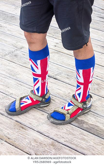 Woman wearing Union Jack flag design socks with sandals on coastal boardwalk on Gran Canaria, Canary Islands, Spain. The Union Jack, or Union flag