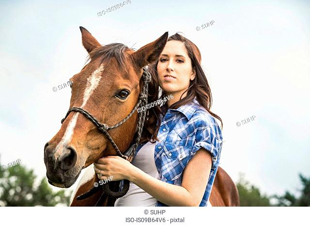 Portrait of young woman standing with horse
