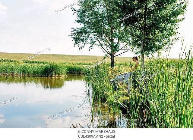 Woman riding grey horse drinking at lake