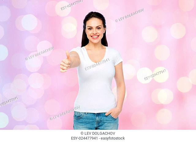 advertisement, gesture, clothing and people concept - happy smiling young woman or teenage girl in white t-shirt showing thumbs up over rose quartz and serenity...