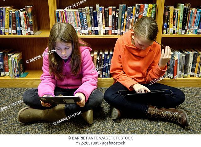 Preteen Girls Using iPads for School Assignment, Wellsville, New York, USA