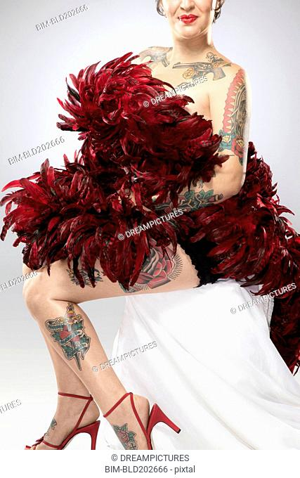 Mixed race woman with tattoos covered with feather boa