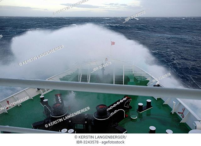 Crossing of the Drake Passage, a big wave is breaking over the bow of the MS Expedition, expedition cruise ship