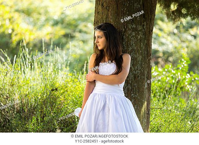 Young bride hiding behind tree