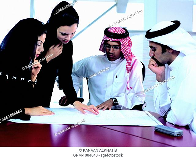 Businesspeople discussing architectural sketch
