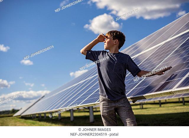 Boy standing next to solar panels
