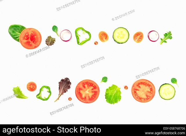 Fresh vegetable salad ingredients, shot from above on a white background. A flat lay composition with tomato, pepper, cucumber, onion slices and mezclun leaves