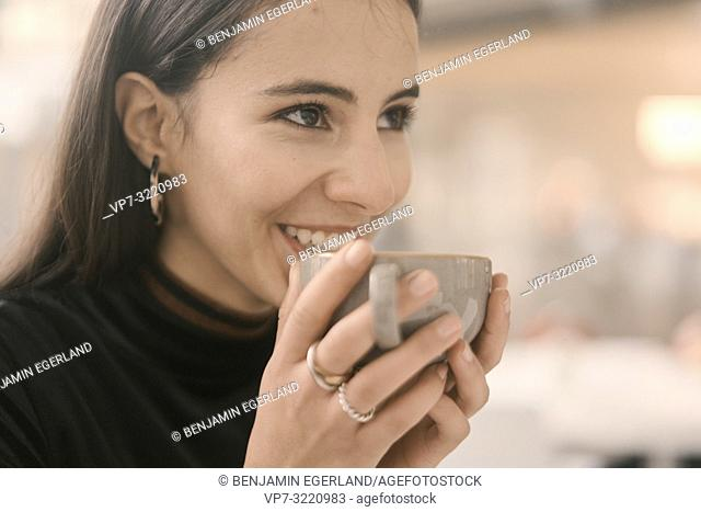 portrait of happy woman holding coffee cup, in Munich, Germany