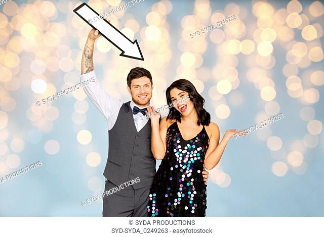 happy couple with big arrow at party