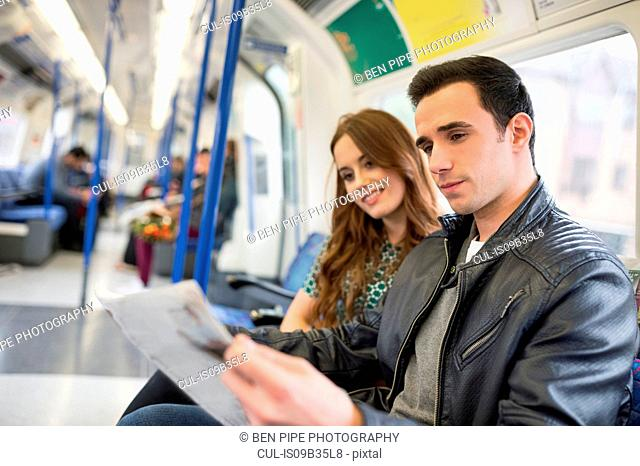 Couple on train reading newspaper