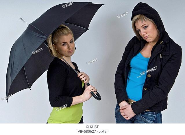 zwei junge Frauen unter schwarzem Regenschirm - Niederoesterreich, Ísterreich, 26/11/2007
