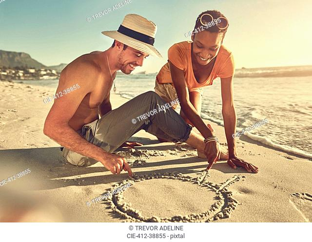 Young couple drawing in sand on sunny summer ocean beach