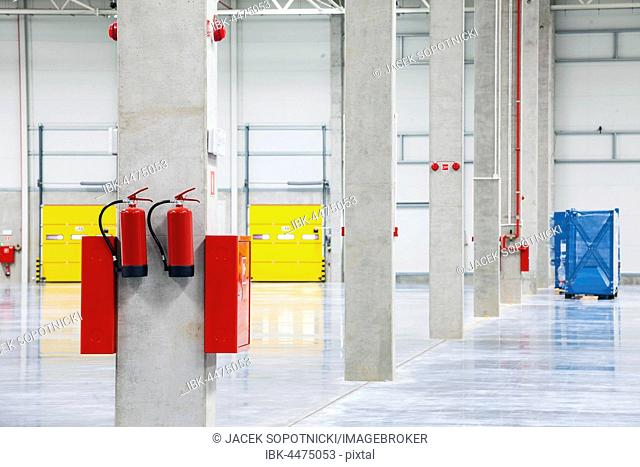 Modern empty storehouse with fire extinguishers
