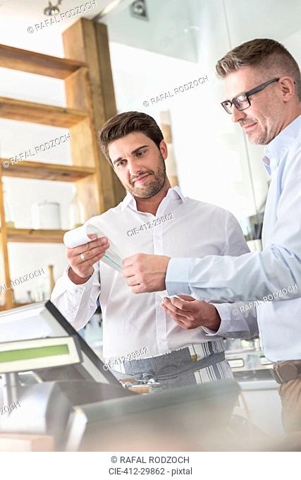 Cafe owner and waiter reviewing receipt at cash register