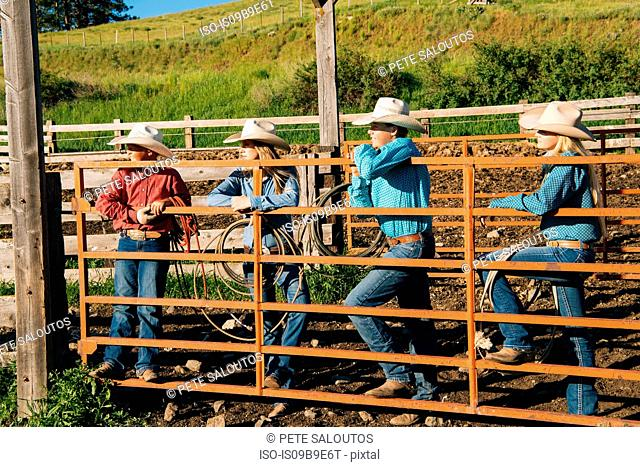 Cowboys and cowgirls leaning on gate, looking away, Enterprise, Oregon, United States, North America