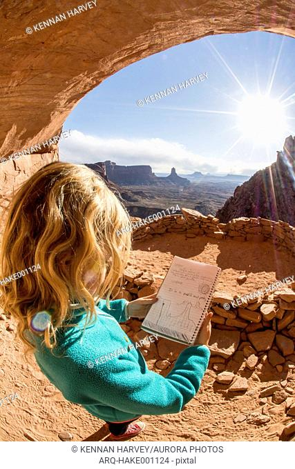 A young girl holding her register art while hiking to the False Kiva, Island in the Sky, Canyonlands National Park, Moab, Utah