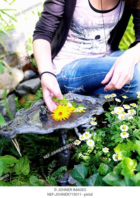 Teenage girl by a birdbath in a garden, Sweden