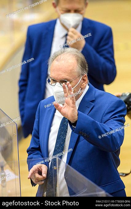 11 March 2021, Saxony-Anhalt, Magdeburg: Reiner Haseloff (CDU), Minister President of Saxony-Anhalt, enters the plenary chamber of the state parliament and...