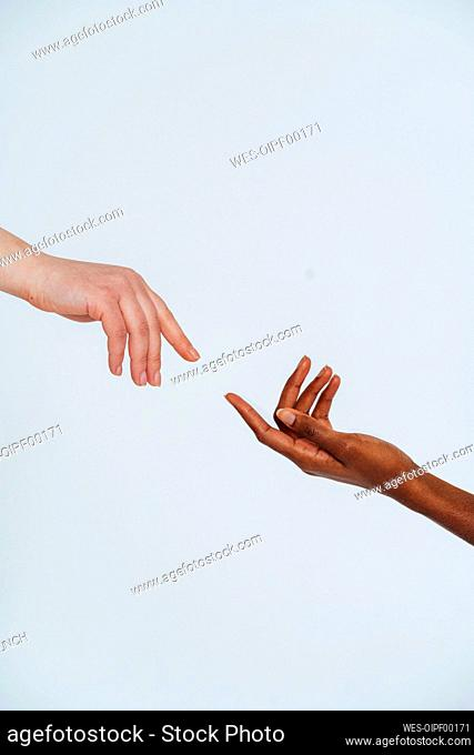 Female friends stretching hands toward each other against white background