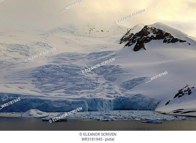 Glacier at sunrise, with atmospheric cloud and mist, Neko Harbour, Andvord Bay, Graham Land, Antarctica, Polar Regions