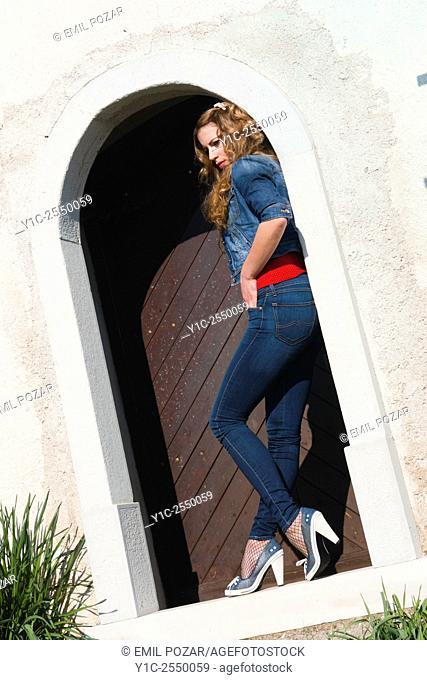 Young woman in denim pants on doorstep