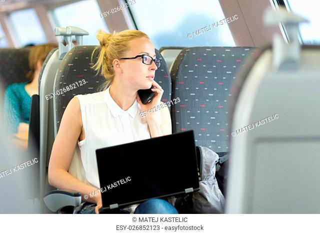 Businesswoman talking on cellphone and working on laptop while traveling by train. Business travel concept