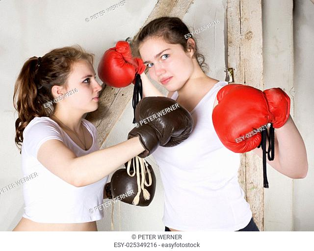 two girls posing as boxers with boxing gloves