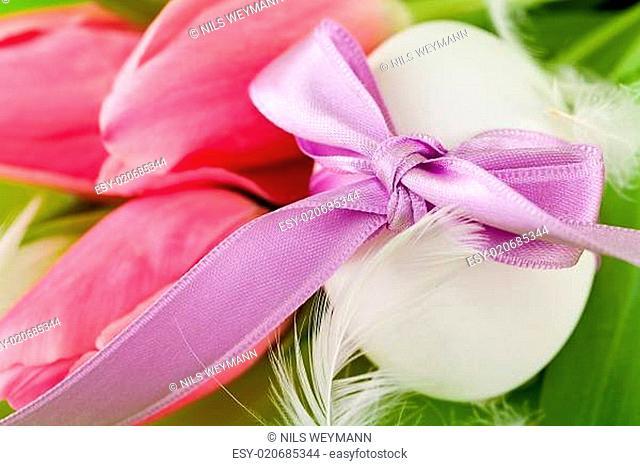 Traditionelle Ostereier Dekoration mit Band Schleife und Tulpen