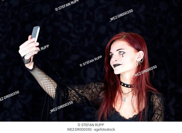 Young woman wearing Gothic fashion photographing herself with smartphone