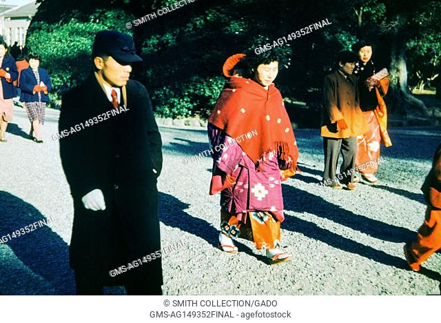 A man wearing a black coat and a serious facial expression walks with a woman who wears traditional geisha dress, including white face paint and a colorful...