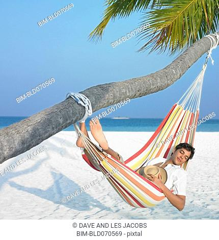 Man sleeping in hammock at beach