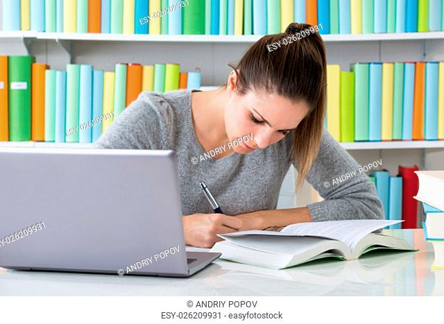Photo Of Happy Young Woman Studying In Library