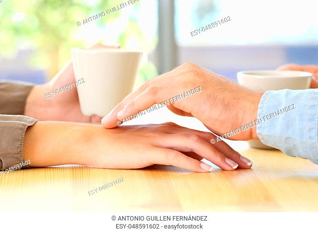 Close up of a man touching the hand of his partner during a date in a table of a coffee shop or home