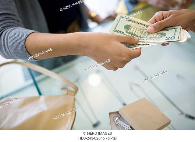 Woman paying cash at shop counter